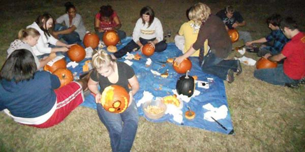 Students carving pumpkins at a cookout